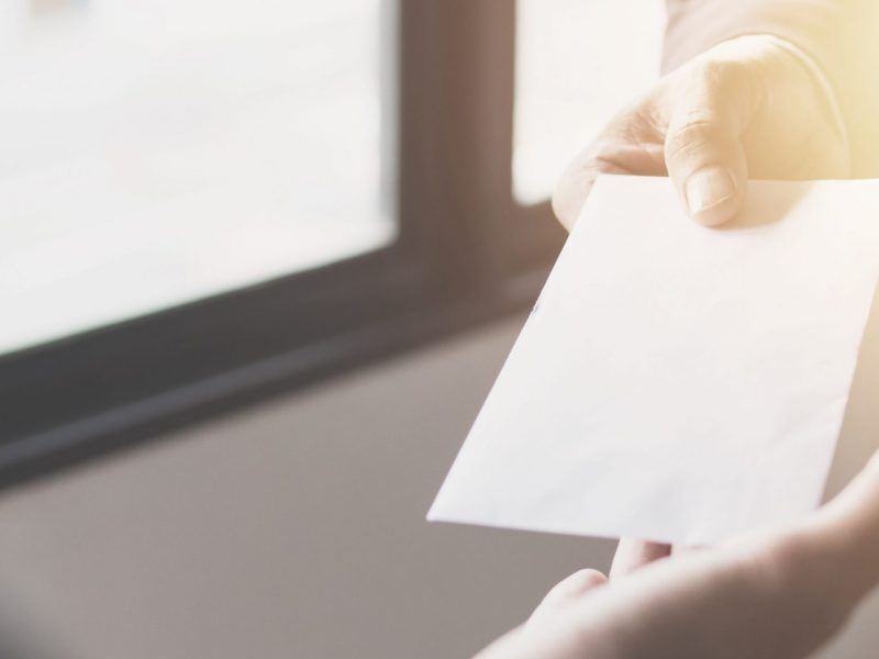 Close up hand of manager giving money bonus in paper envelope to happy office worker,congratulating employee with increasing of salary or promotion as new position